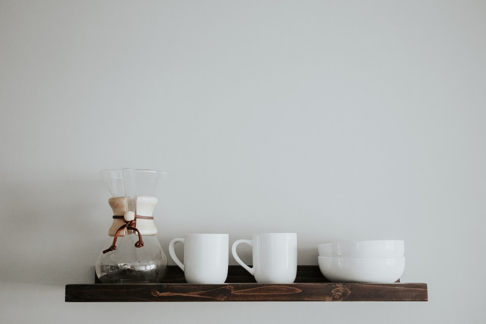 two white ceramic mugs on brown wooden wall-mount shelf