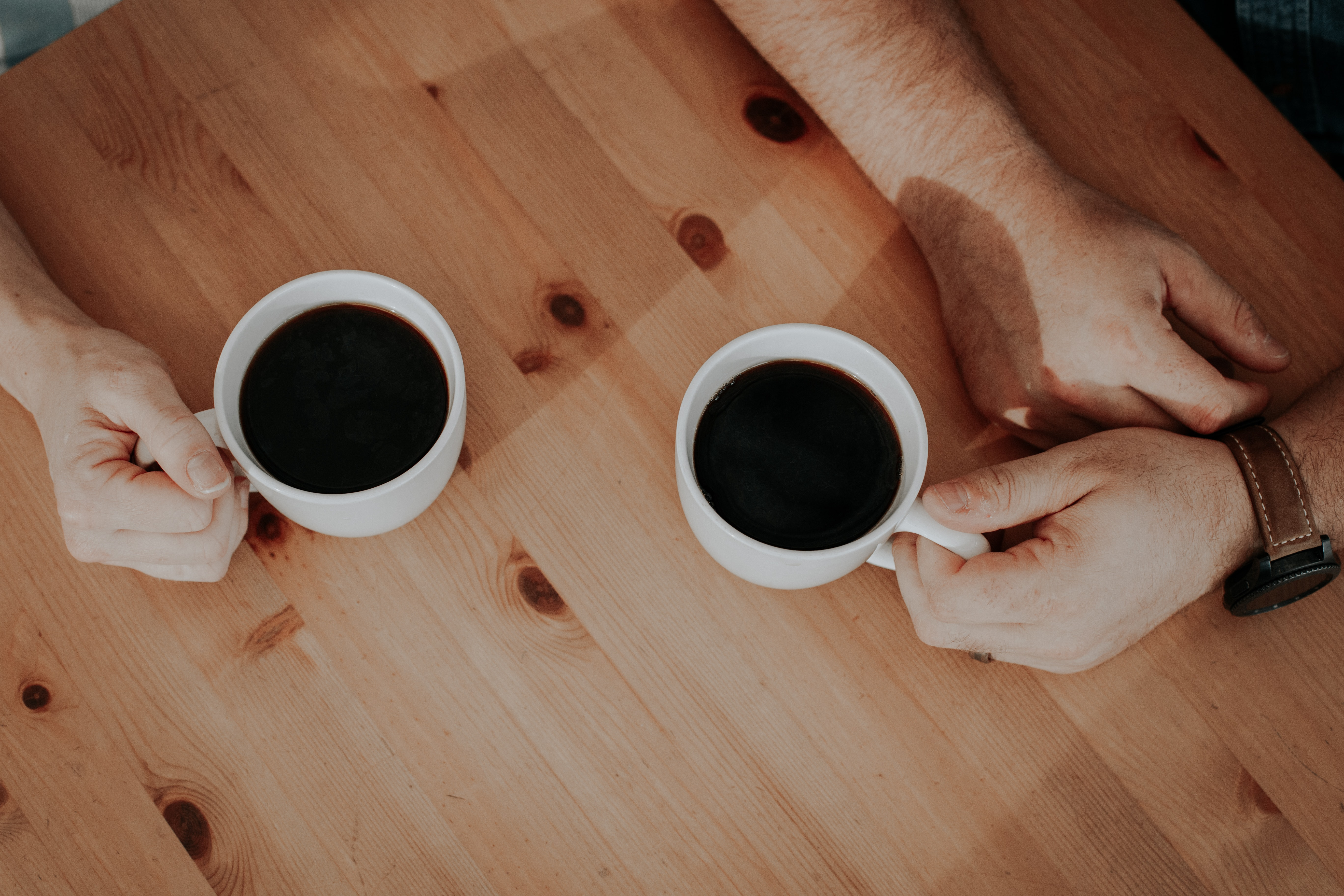 two person holding white mugs filled with coffee's on brown surface
