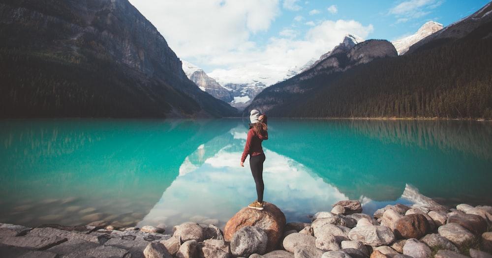 woman standing on brown rock taken at daytime