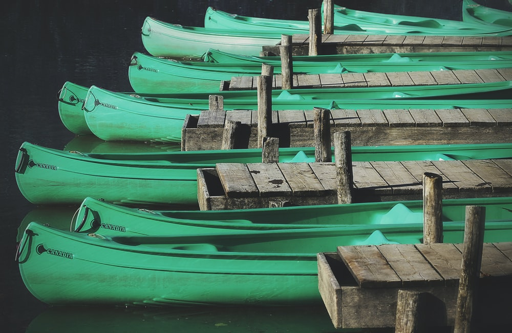 green wooden canoes docks near gray wooden sea docks