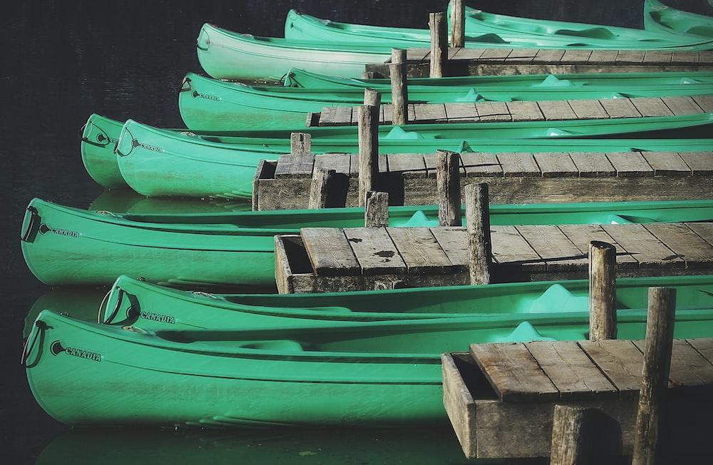 green wooden canoes docks near gray wooden sea docks