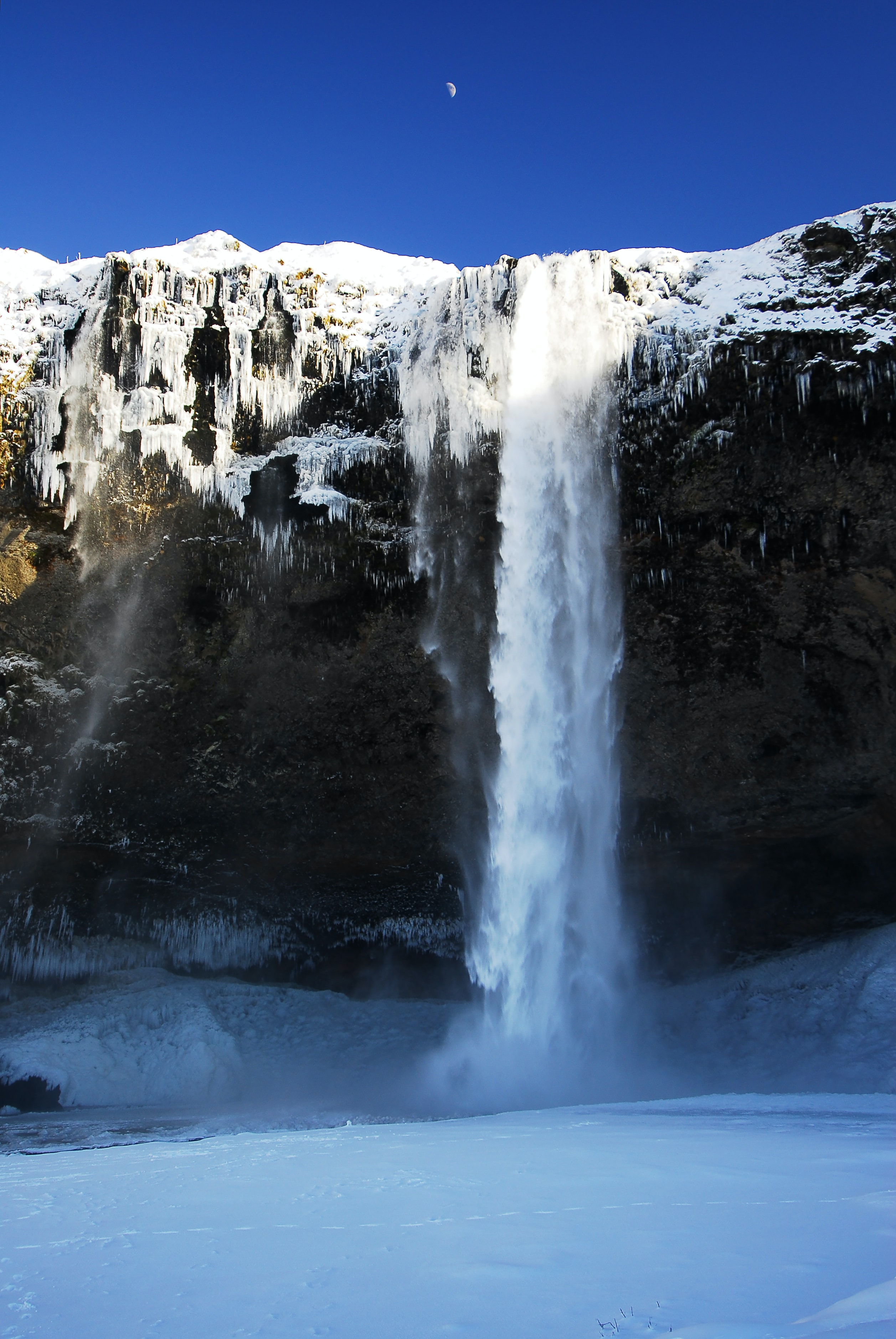 waterfalls on black and white mountain during daytime