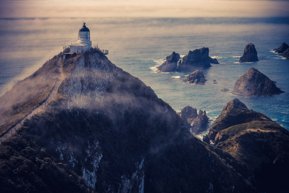 aerial view of a lighthouse atop of mountain