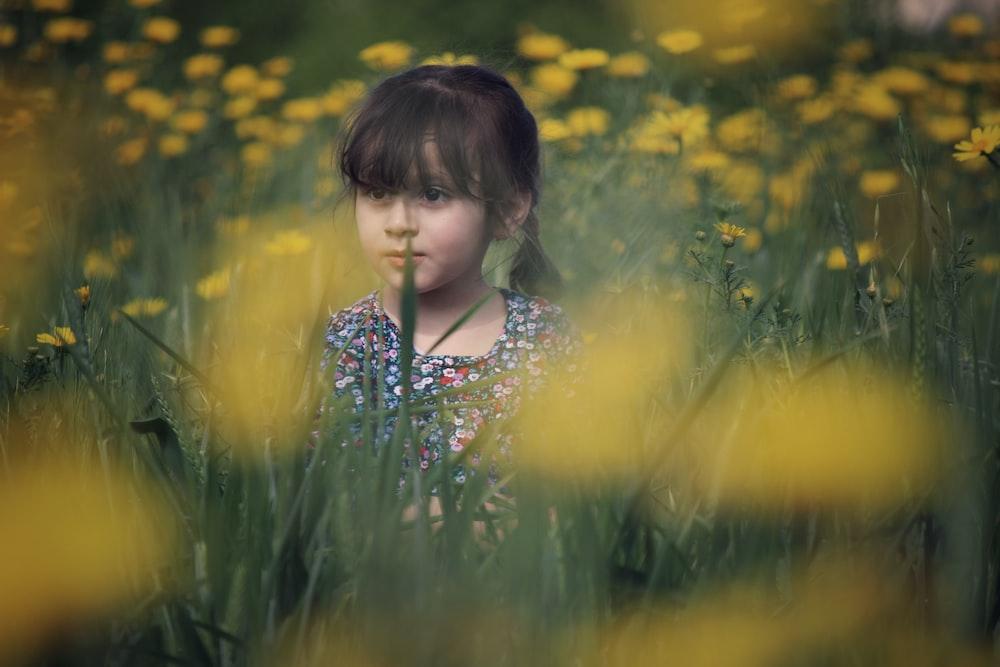 girl wearing multicolored top on yellow petaled flower field