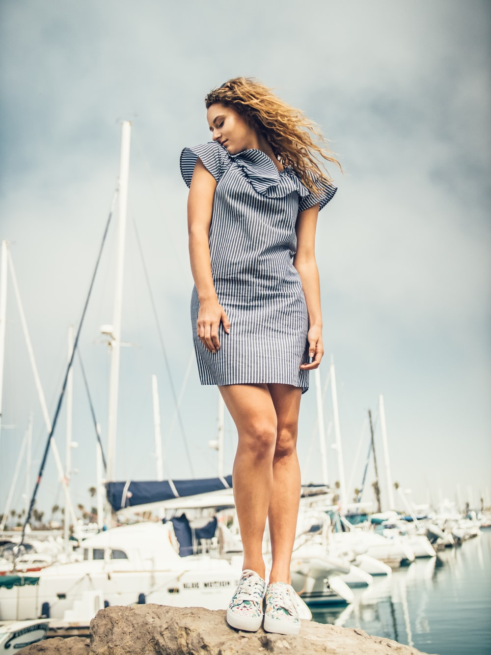 woman standing on rock near yachts during daytime
