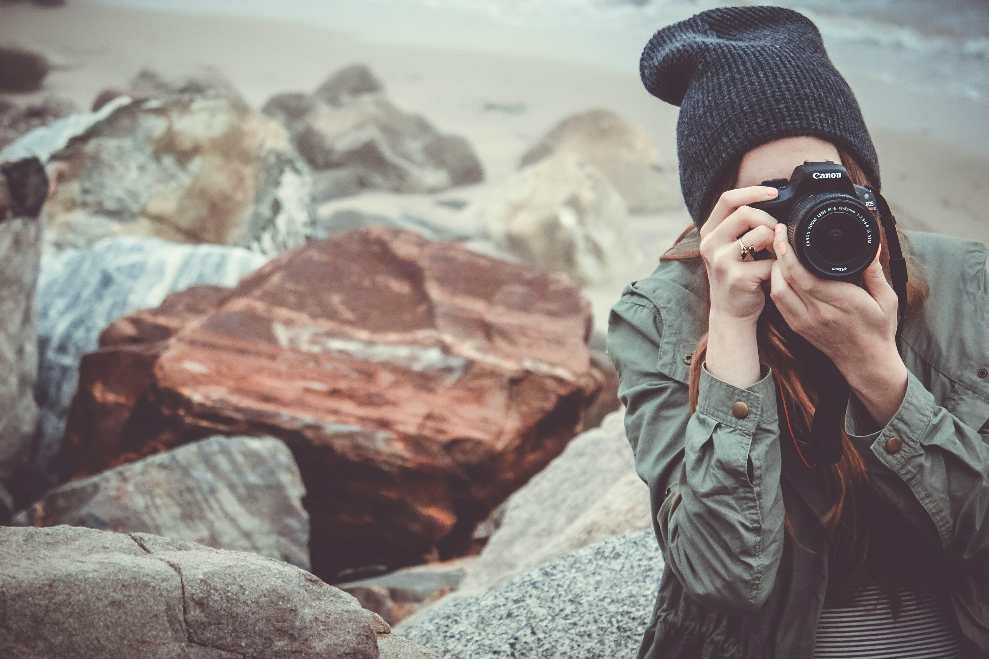 woman wearing gray jacket and black knit cap holding black Canon DSLR camera near big rocks at daytime