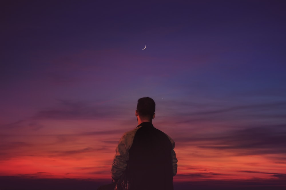 man in black jacket looking at the moon