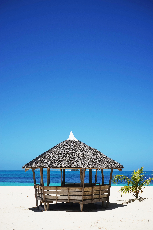 brown wooden nipa hut on white sand near body of water