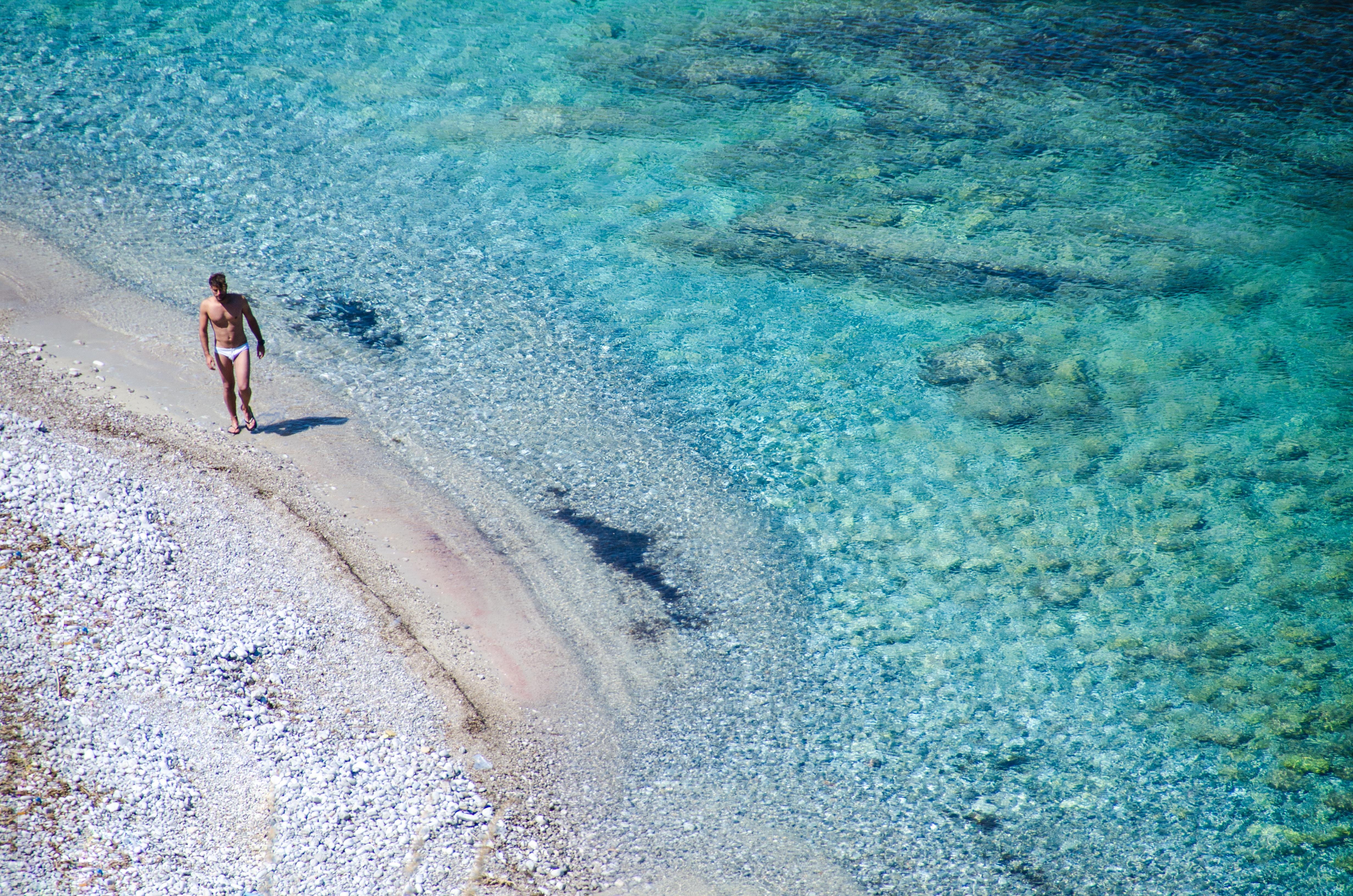 man walking on seashore beside blue se