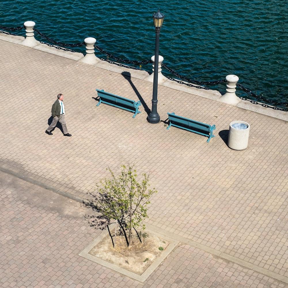 man walking near body of water during day