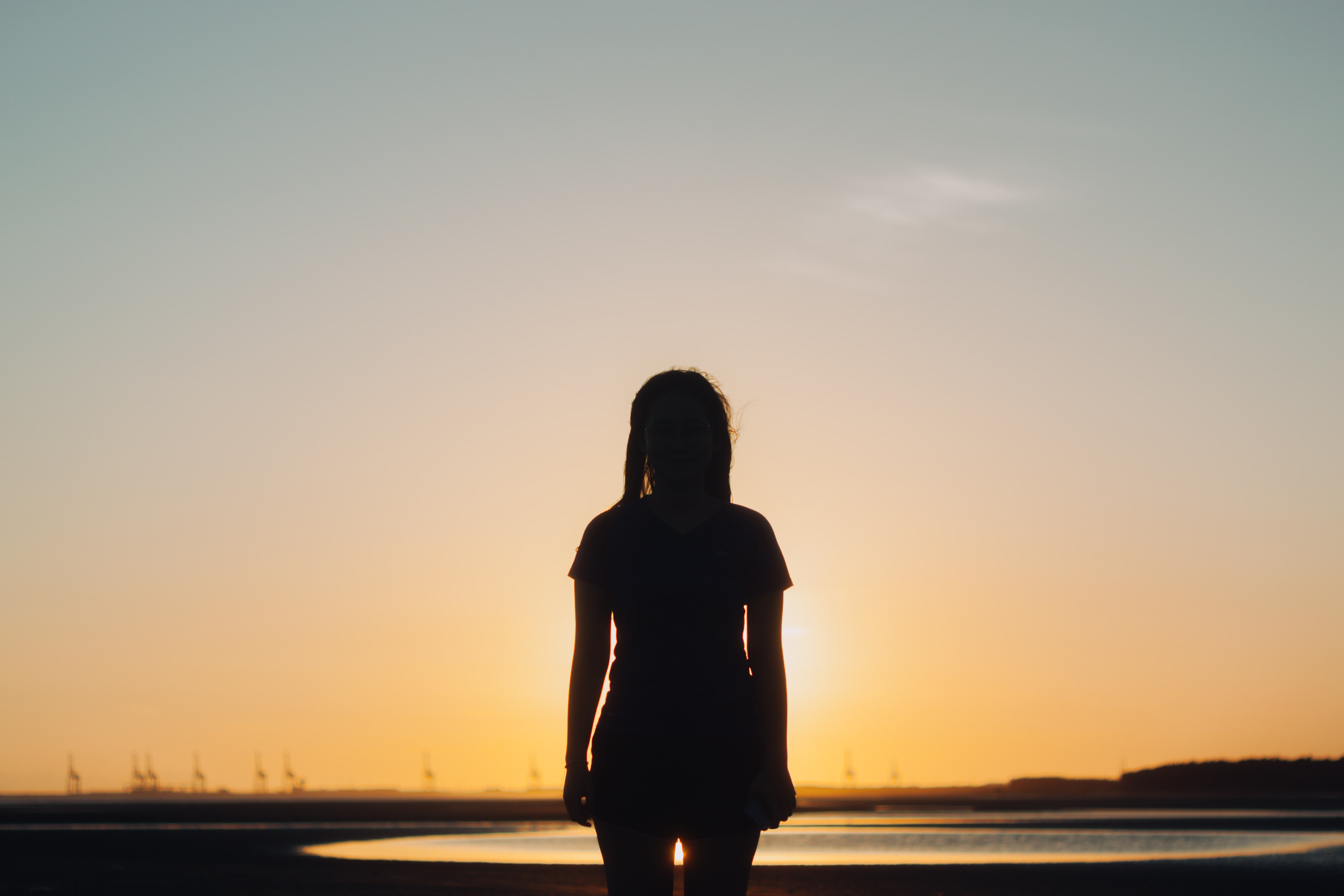 silhouette photography of woman standing in front of body of water