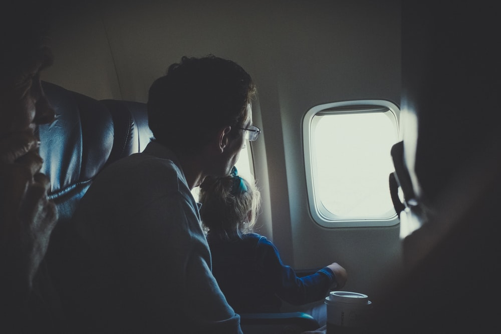 man and girl sitting inside airplane during daytime
