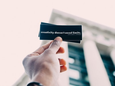 person holding black and white quote-printed card creativity teams background