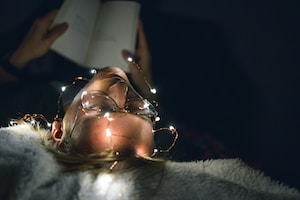 man reading book with string lights turned on
