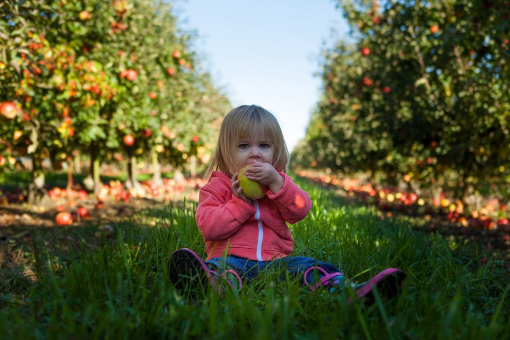 girl sitting on green grass field holding green fruit during daytime