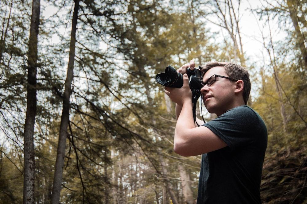 man wearing black shirt taking photo of wilderness