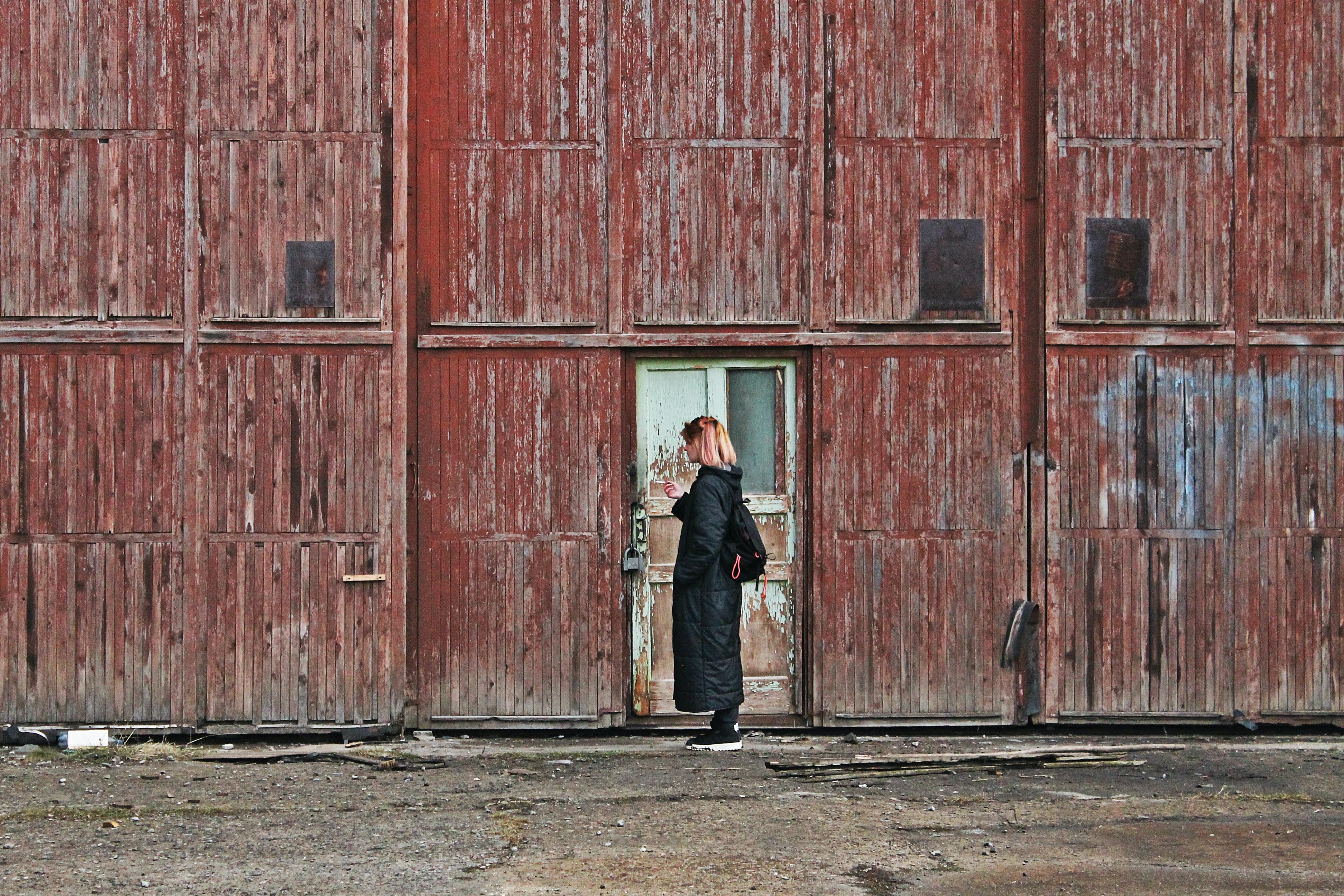 woman wearing black jacket near white wooden door