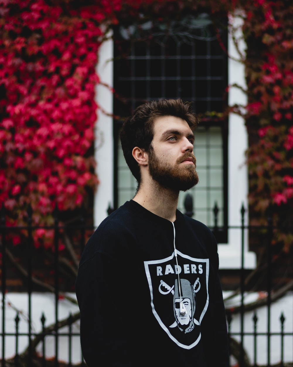man in black Oakland Raiders long-sleeved shirt