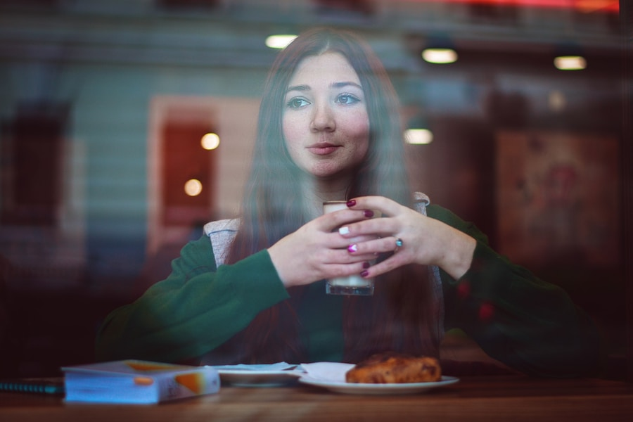 woman in green sweater sitting in front of table holding drinking glass