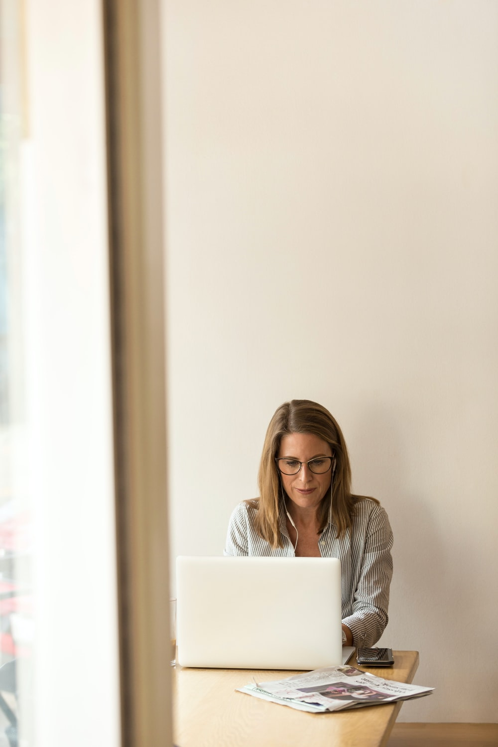 woman wearing grey striped dress shirt sitting down near brown wooden table in front of white laptop computer