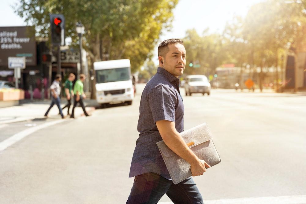 man holding bag walking on road