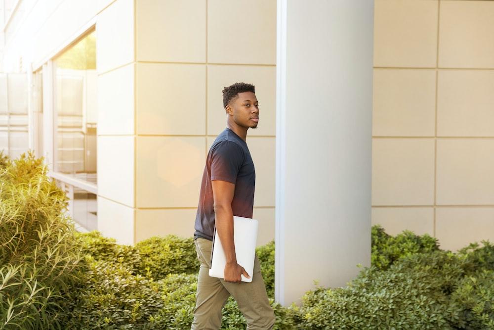 man holding laptop walking towards building