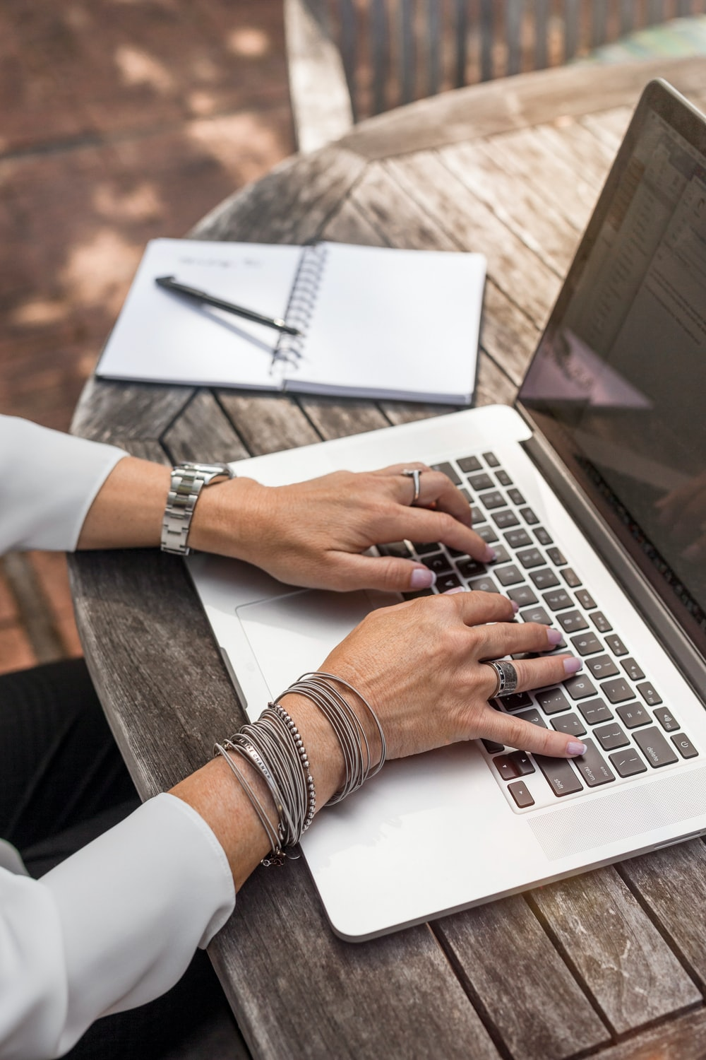 person typing on MacBook Pro on brown wooden table during daytime photo
