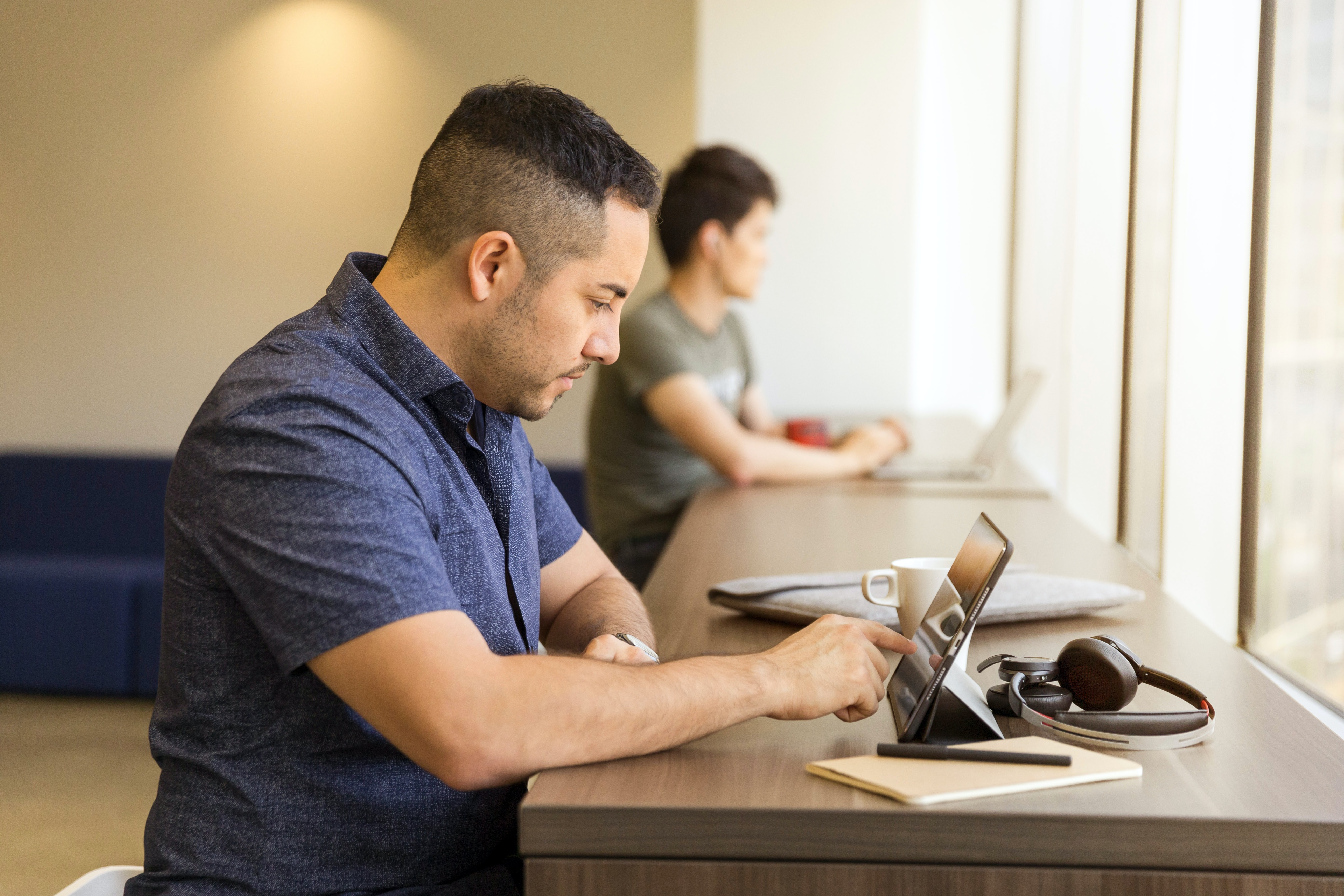 man touching tablet computer on desk
