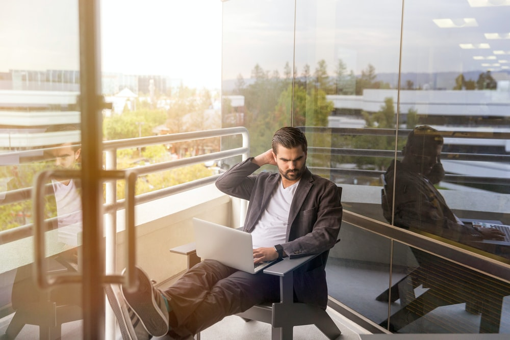 man sitting on gray arm chair using silver laptop computer on building balcony at daytime