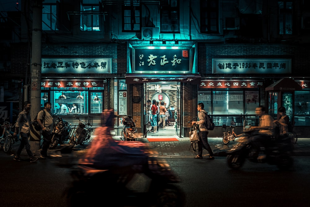 motorcycles and people passing by at night time