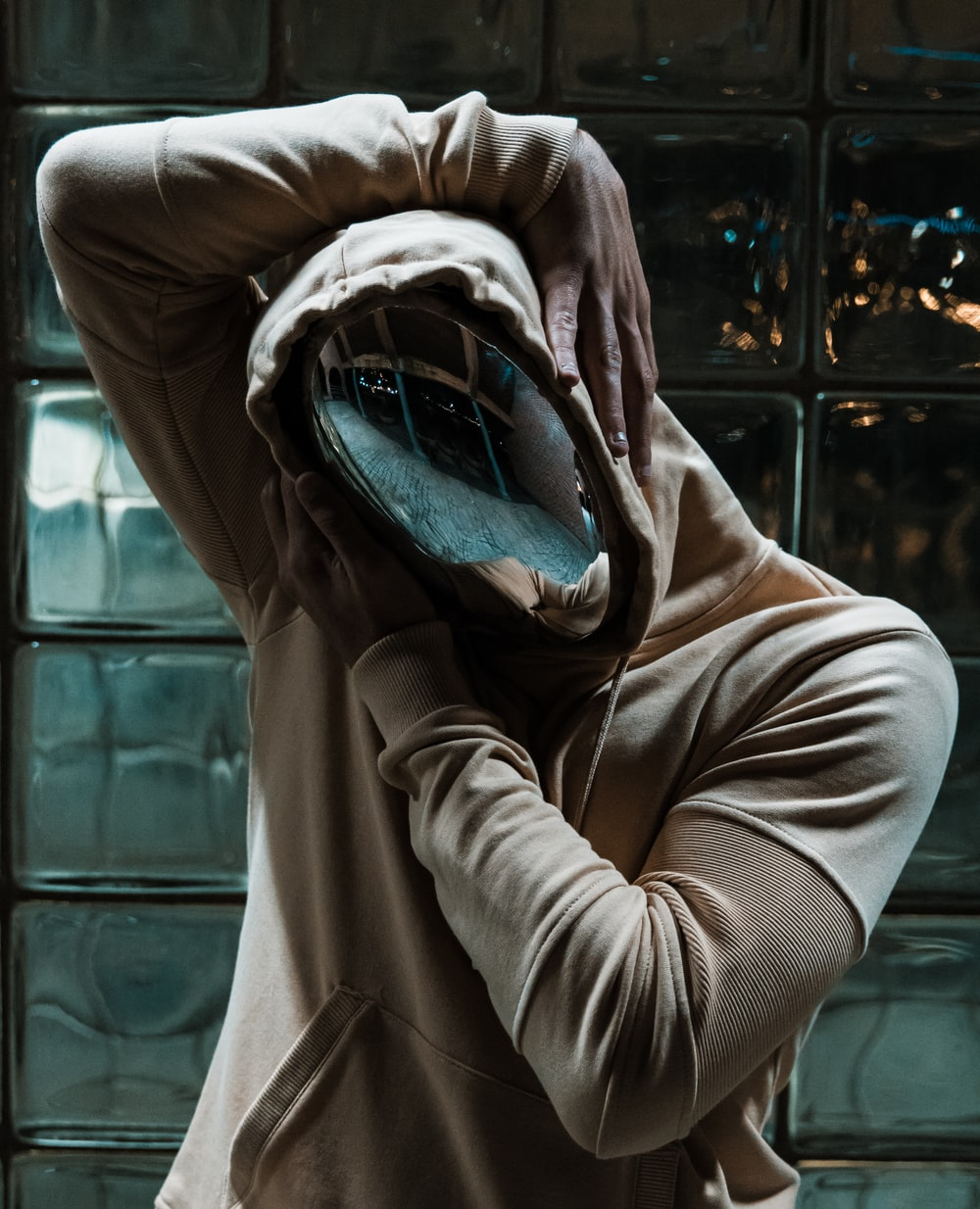 person in chrome mask and pullover hoodie behind clear glass wall