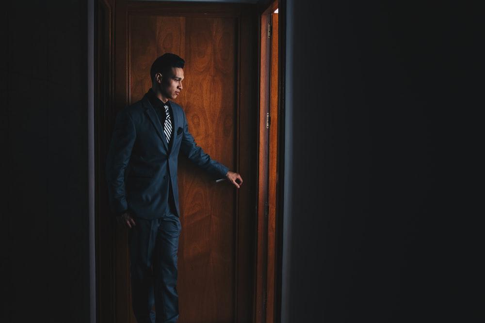 man wearing black suit jacket and dress pants standing beside brown wooden door