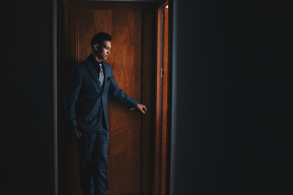 man wearing black suit jacket and dress pants standing beside brown wooden door