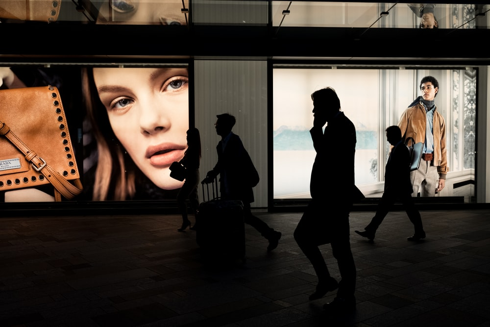 silhoutte of three persons near billboard