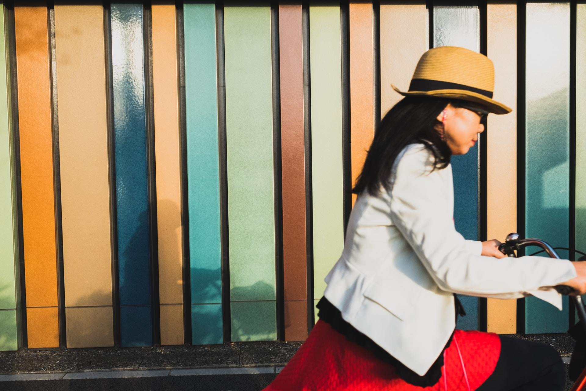 woman wearing white blazer and brown hat riding bicycle