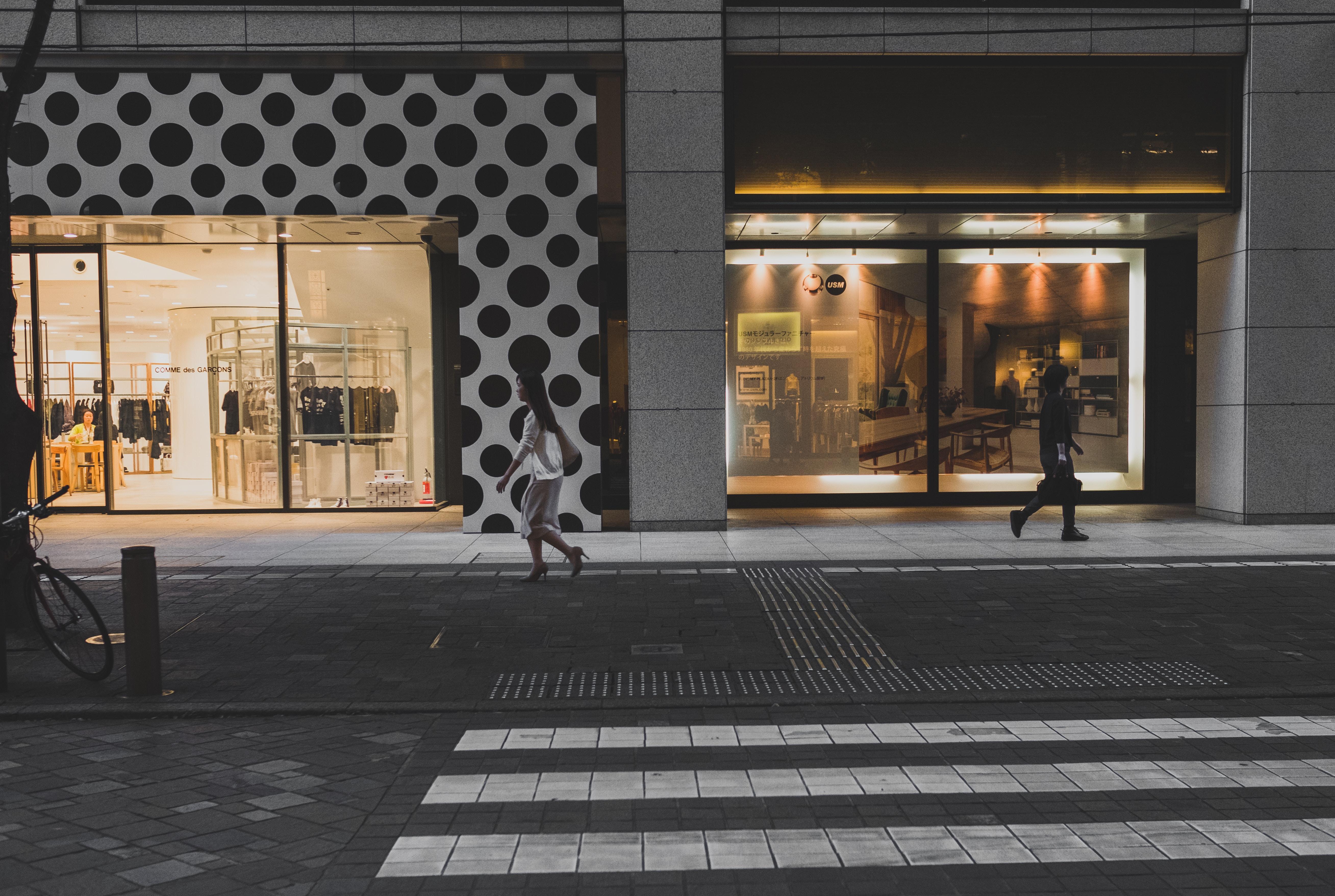 two women walking beside store