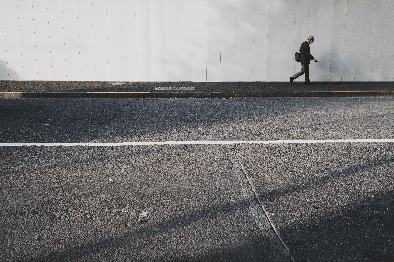 person walking near white wall