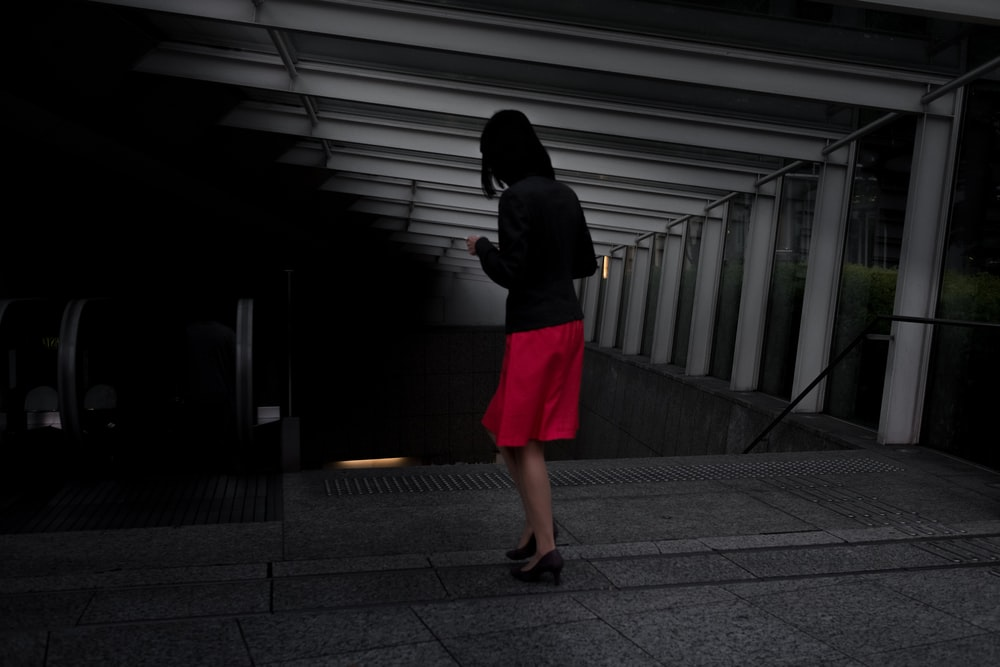 woman in black long-sleeved shirt and red skirt