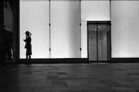 silhouette of woman near glass wall