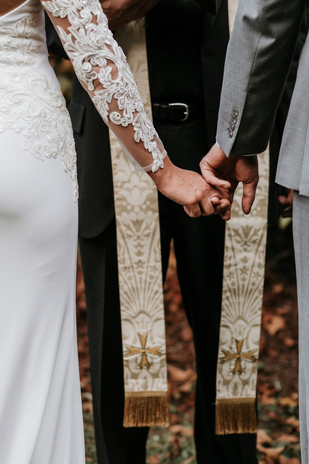 man and woman holding hands in front of priest during daytime