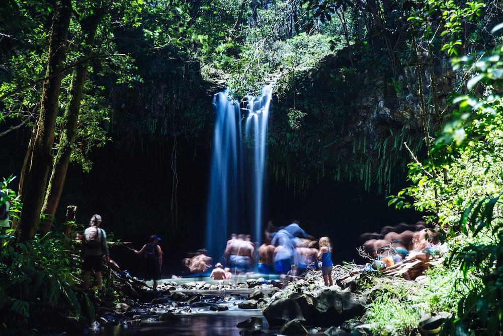 people near waterfalls during daytime