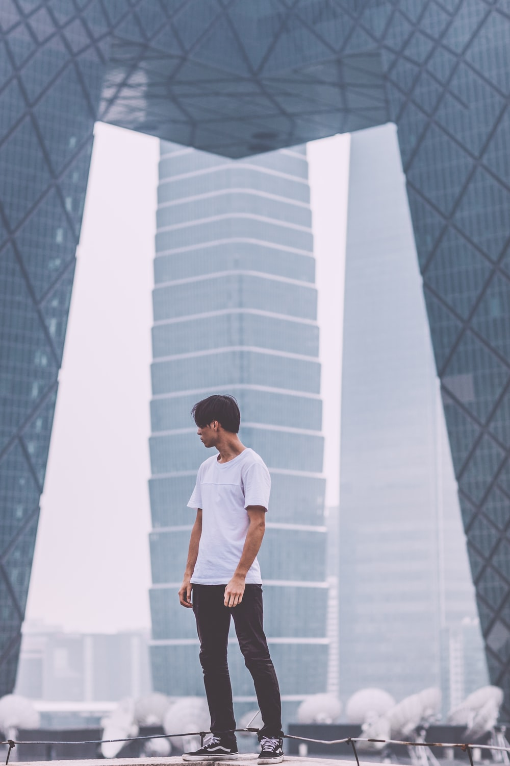 man wearing white crew-neck shirt standing near the building
