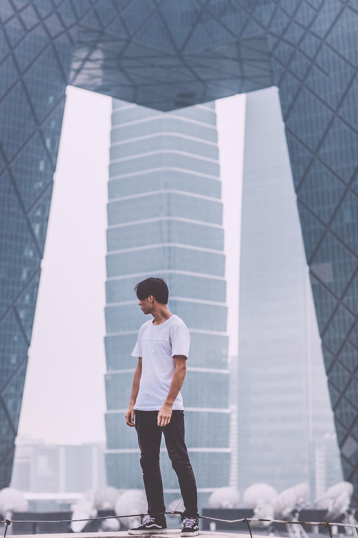 man wearing white crew-neck shirt standing near the building