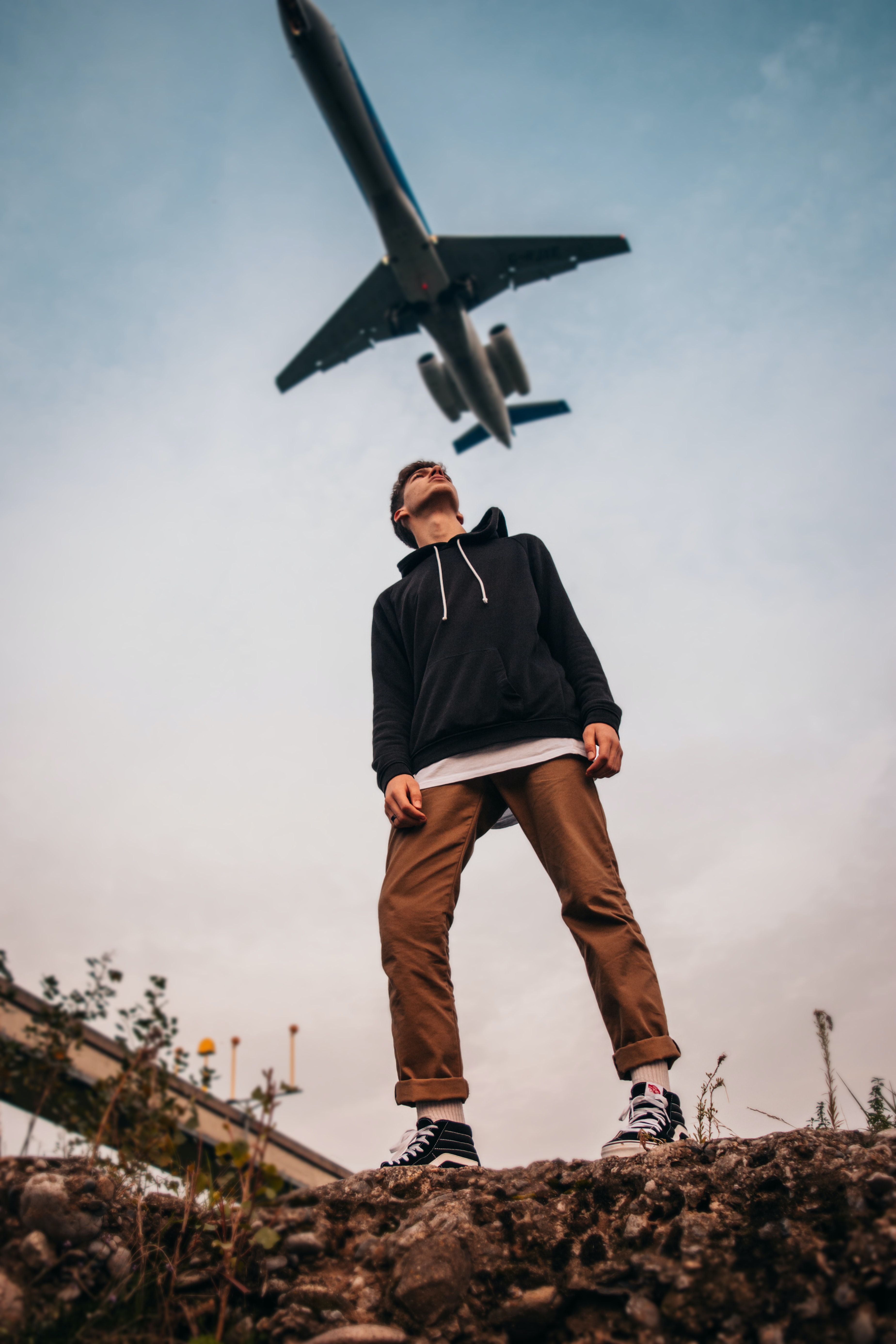 man looking up at flying airplane during daytime