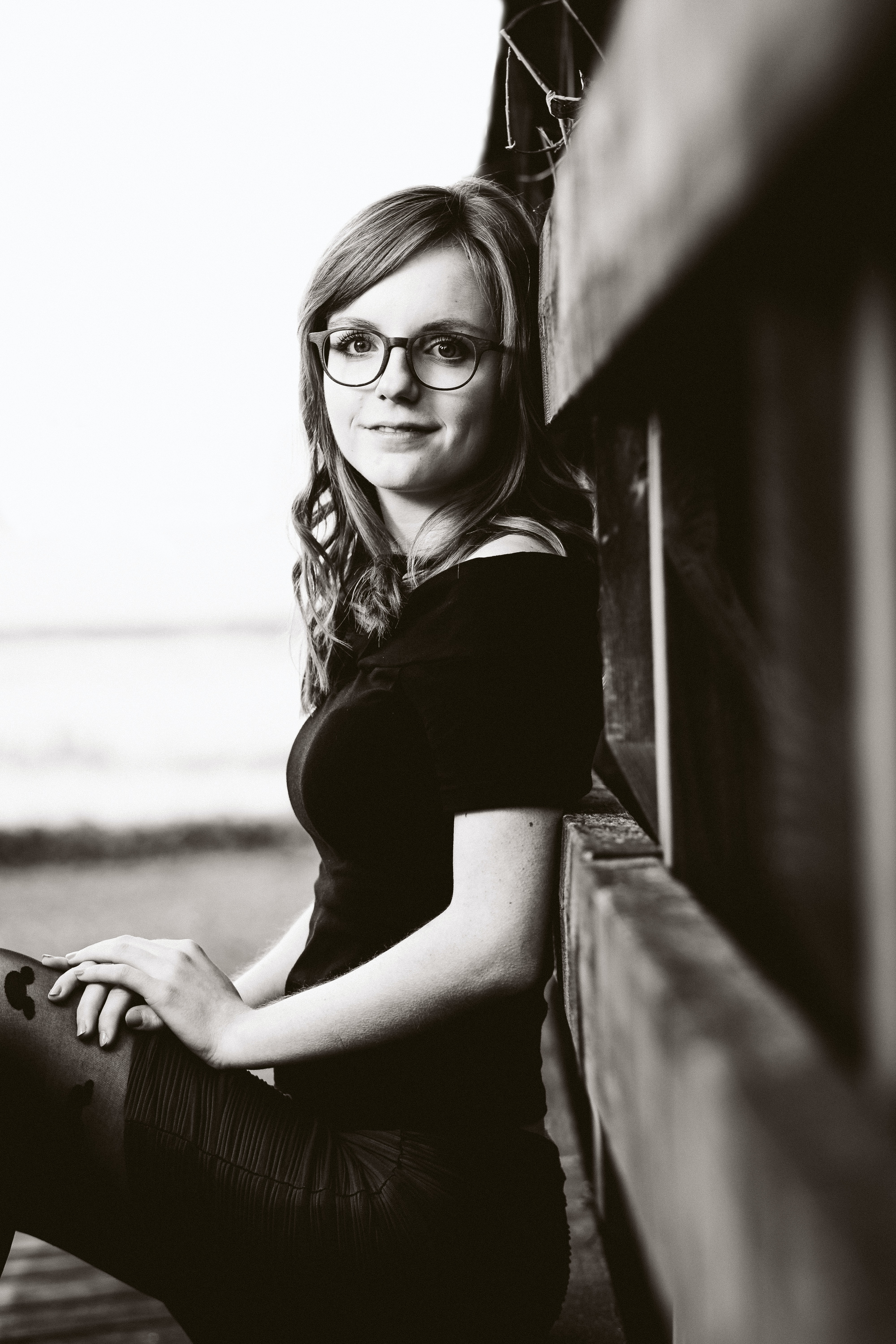 grayscale photo of woman lean on wall