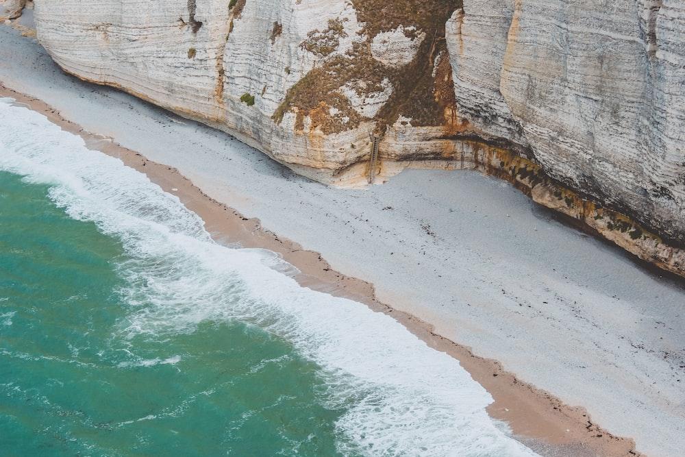 bird's eye view photo of seashore beside cliff