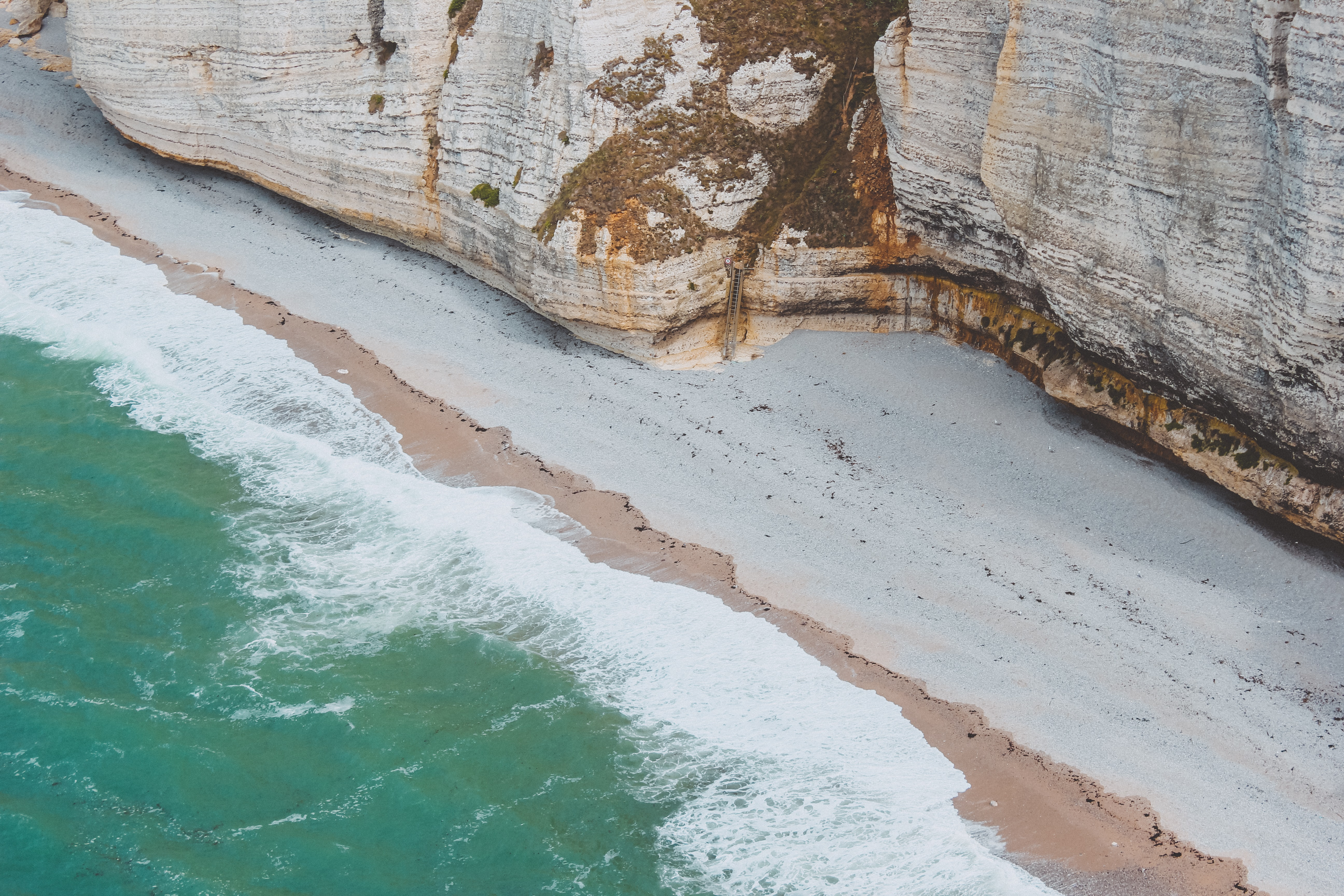 bird's eye view photo of seashore beside cliff