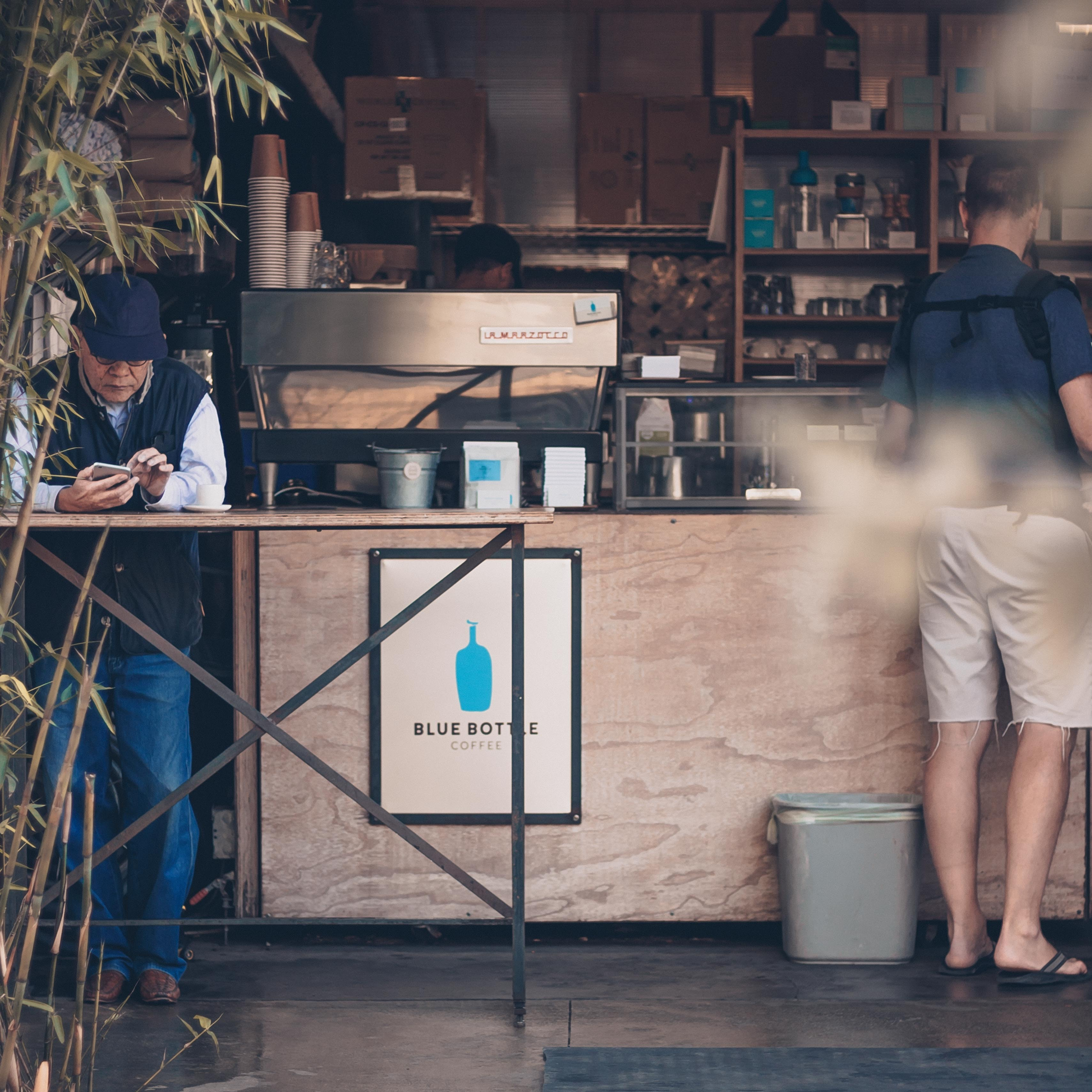 man leaning on table in front of coffee store