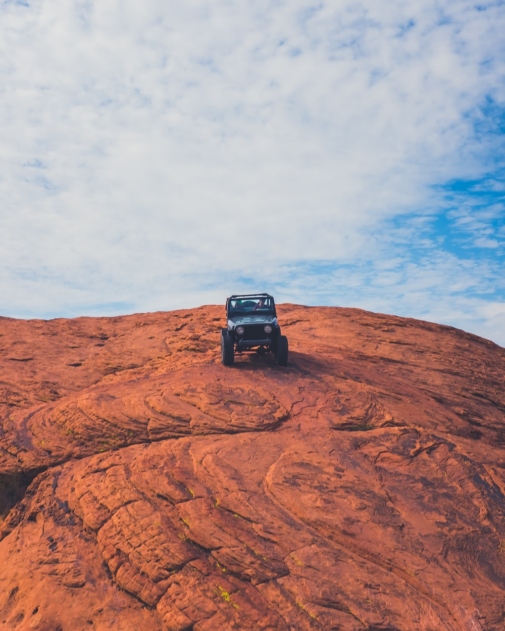 Jeep SUV on top of rock