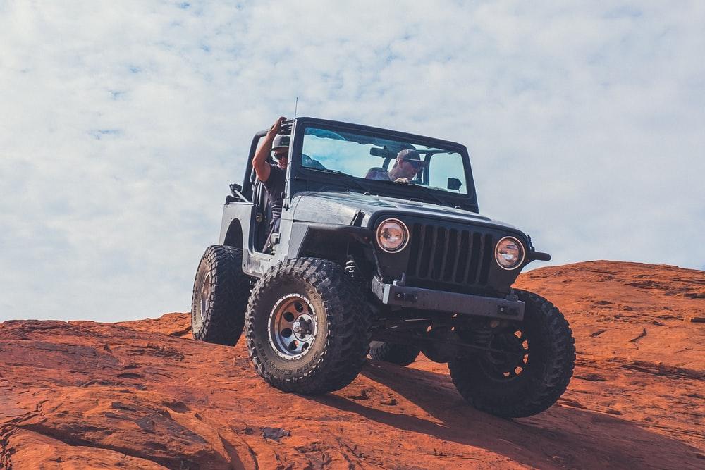 black Jeep Wrangler on brown field under cloudy sky during daytime
